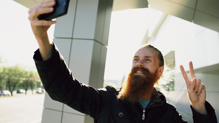 Young bearded hipster man taking selfie picture using smartphone camera outdoors at city street