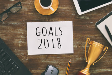Top view 2018 goals list with gold trophy, cup of coffee and computer keyboard over wooden desk.