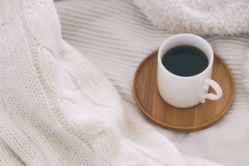 Cup of coffee over cozy and white blanket. Top view.