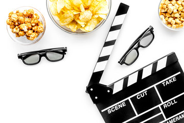 Fast food for watching film. Popcorn, crisps, rusks near glasses and clapperboard on white background top view copyspace