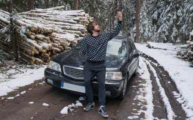 Man making selfie on the phone near car in winter forest