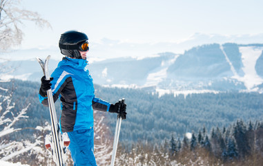 Happy female skier enjoying stunning scenery in the winter mountains ski resort, looking away, holding skis, wearing blue ski suit and black helmet copyspace