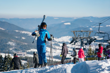 Full length shot of a happy woman posing with her skis on the shoulder on top of the hill, smiling joyfully. Blue sky, mountains, forests, ski lift and people on the blurred background