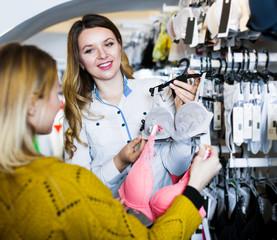 Woman seller assisting woman in choosing bra