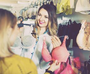 Female seller demonstrating client bras in underwear store