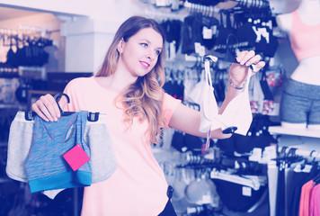 Young female shopper examining sports underwear