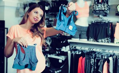 Young girl shopper examining sports underwear