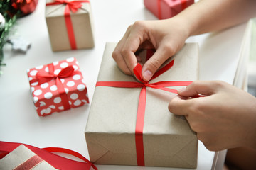 Female hands wrapping  present boxes.