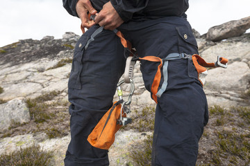 Mountain climber putting on safety harness, Chilliwack, British Columbia, Canada