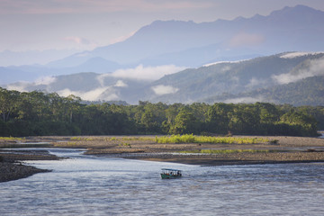 View of the Alto (Upper) Madre de Dios River in Peru. Surrounded by jungle, with boat in morning light and clouds.
