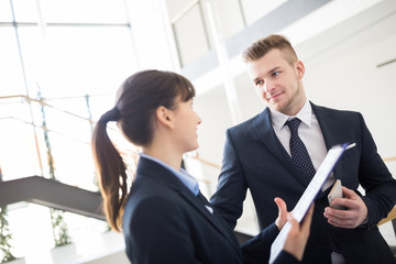 Junge Geschäftsfrau bespricht sich mit einem Kollegen