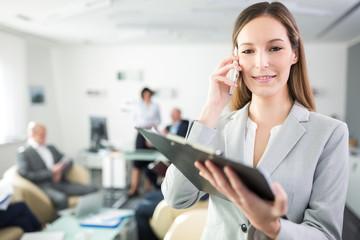 Junge Geschäftsfrau telefoniert mit Smartphone