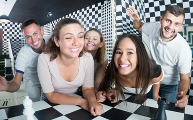 Men and women on chessboard in quest room