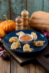 Traditional Asian dish. Crescent shape imperfect dumplings with spicy sauce served with garlic, onion and pumpkin on oak board