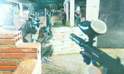 Paintball players aiming in opponents
