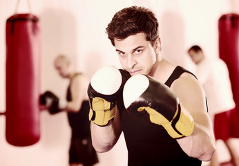 active sportsman in the boxing hall practicing boxing punches