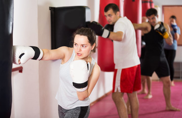 Young athlete female is beating a boxing bag