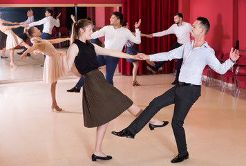 Friendly people dancing lindy hop in pairs