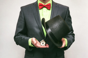 Real estate agent. Insurance agent. Realtor man takes a toy house out of his hat.