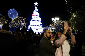 A family takes a selfie during a Christmas tree lighting ceremony at central Syntagma square in Athens