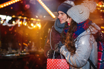 Couple with shopping bag on traditional Christmas market, Holidays shopping