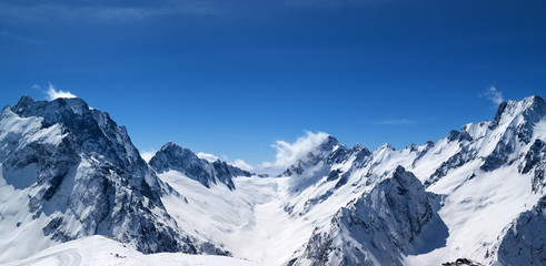Fototapete - Panoramic view of snow covered mountain peaks