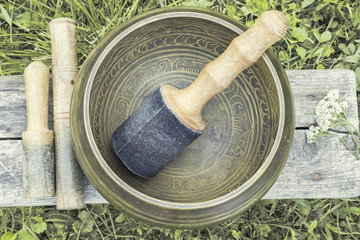 Tibetan Singing Bowl with wooden mallets  on a wood background. Top view composition. Photo with vintage toning.