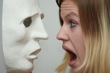 Young blonde girl holding a white theatrical mask
