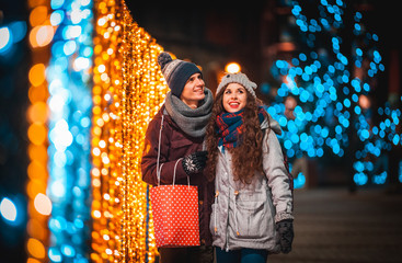 Couple with gift bag on Christmas lights background, walking in the city at evening