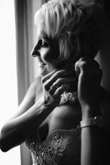 stylish luxury gorgeous blonde bride posing on the background hotel room