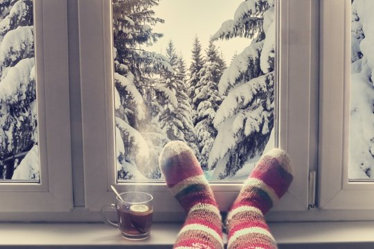 feet in wool knitted socks and a cup of steaming tea on the windowsill overlooking the winter snow forest through the window