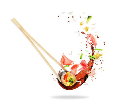 Piece of sushi sandwiched between chopsticks with splashes of soy sauce, isolated on white background