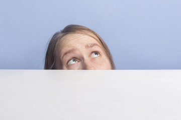 brown-haired girl looks up in surprise behind white banner, isolated on blue background