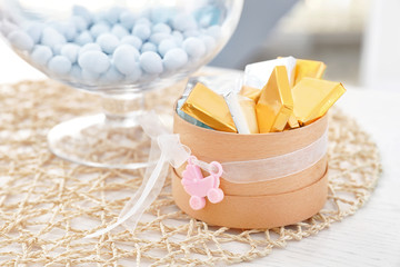 Box with treats for baby shower party on table