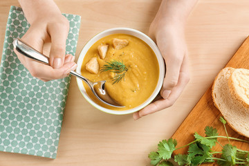 Woman holding bowl of homemade lentils creme soup on table