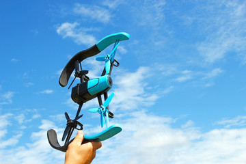 Man hand holds high the blue drone, which is isolated on the blue cloudy sky in summer time