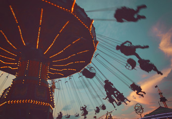 local fair at dusk with people riding swinging rides and enjoying the summer atmosphere toned with a retro vintage instagram filter app or action