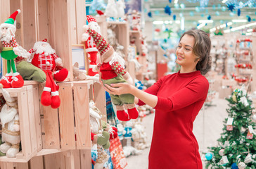 Cheerful happy customer girl choosing gifts for Christmas and New Year. She is holding Santa toys. Happy moments. Family care