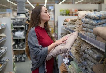 Customer woman chooses bed linen and bed in the supermarket mall store. She is examining sofa pillow.