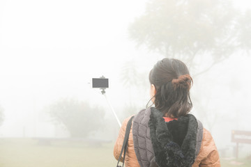 woman use smart phone to take selfie photo in mist and fog. tourist take photo in forest.
