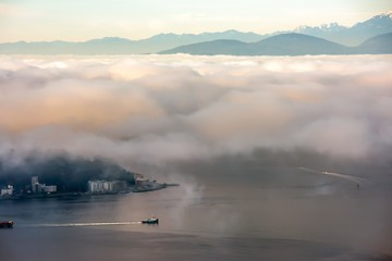A Foggy morning in Seattle over Puget sound with a boat below and the Olympic Mountains above Wall mural