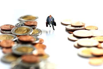 Miniature People : businessman walking between stack of coins