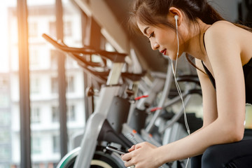 Asian woman exercising in the gym, Young woman workout in fitness for her healthy and office girl lifestyle. She using smart phone to check an email or social network.