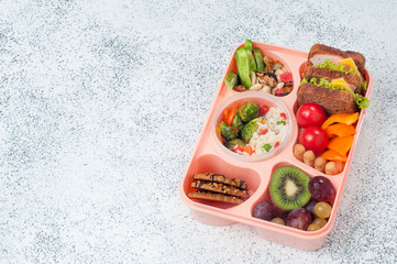 Open lunch box with sandwiches on a grey background with copy space