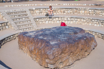 Tourist looking at Hoba meteorite, Namibia, Africa. The meteorite is composed by high density heavy metals, mostly iron and nickel with traces of cobalt.
