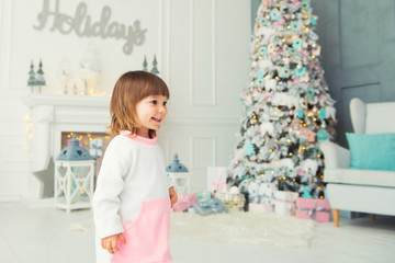 Emotional little girl. Happy New Year. Pleasure, happiness and delight from New Year's gifts.