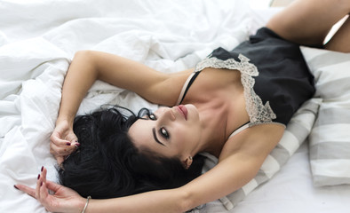 young beautiful sexy woman in black lace lingerie lying on bed