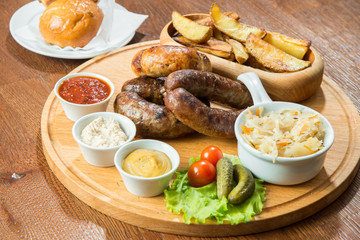 Bavarian fried sausages with potatoes and sauces, on a wooden tray