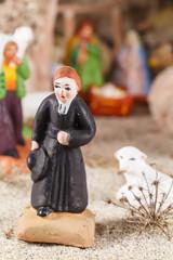 Santon de curé devant crèche de Noël