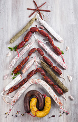 Christmas tree made of sausage on a background of a wooden wall
